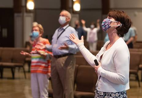 Barbara Layden (front) joins with other parishioners in giving praise during worship at Franklin (Tenn.) First United Methodist Church. The church has adopted safety protocols, including no congregational singing, to help prevent the possible spread of COVID-19. Photo by Mike DuBose, UM News..